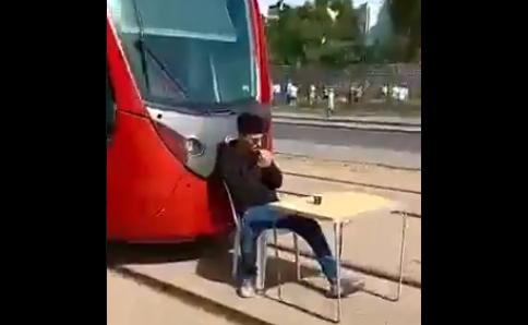 شاب طائش يعرقل الترامواي ليشرب قهوة ويدخن سيجارة وسط سكته يثير موجة غضب (فيديو)